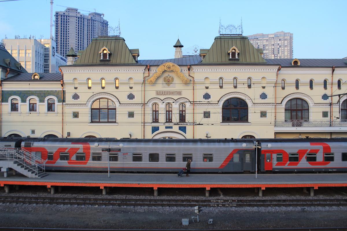 eine Frau zieht Ihren Koffer über den Bahnhof Wladiwostok